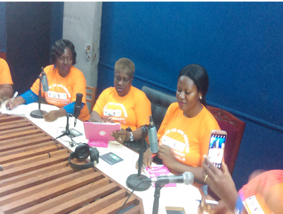 women in orange t shirt sitting in a studio